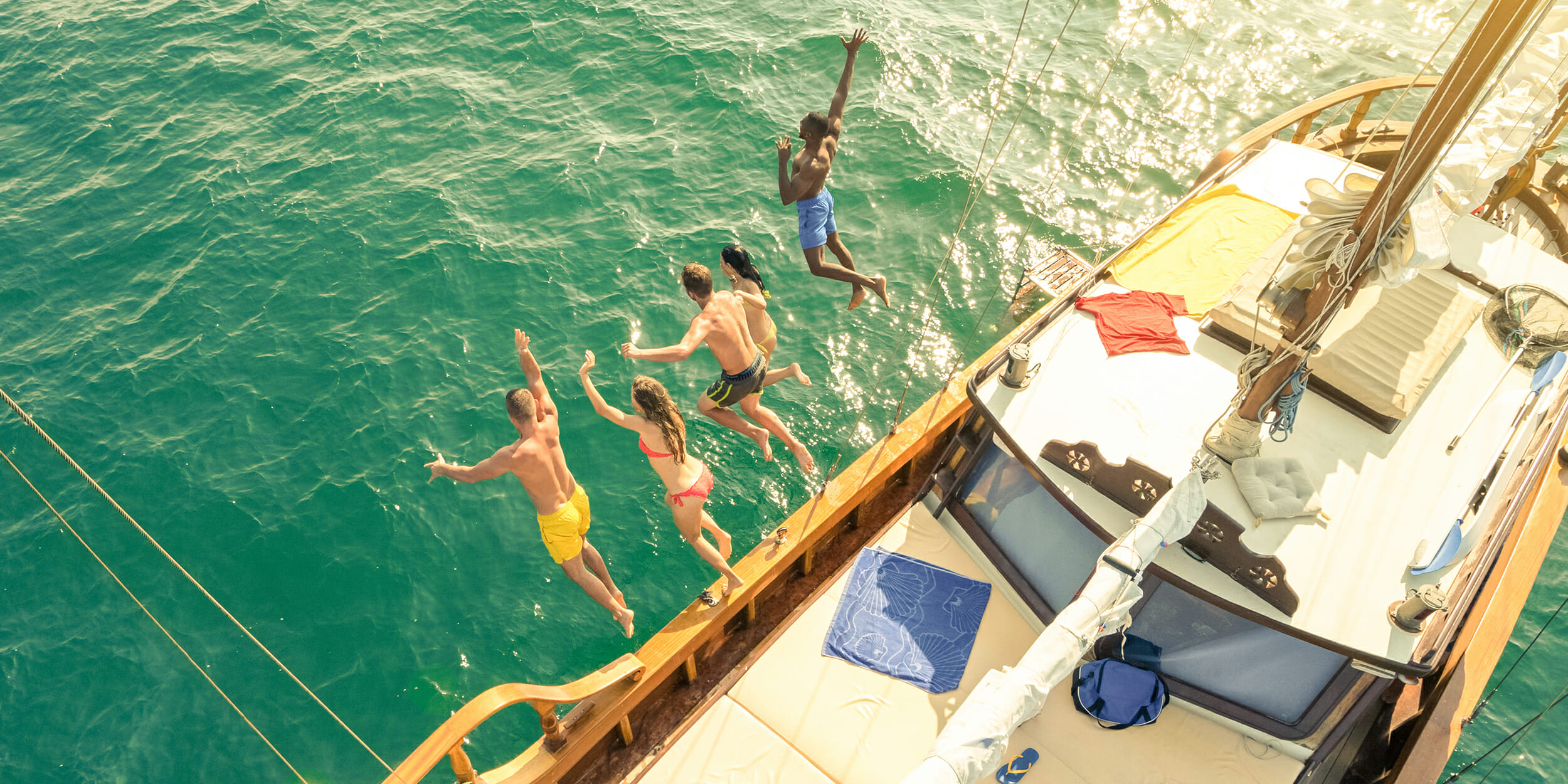 People jumping off of a boat into the water