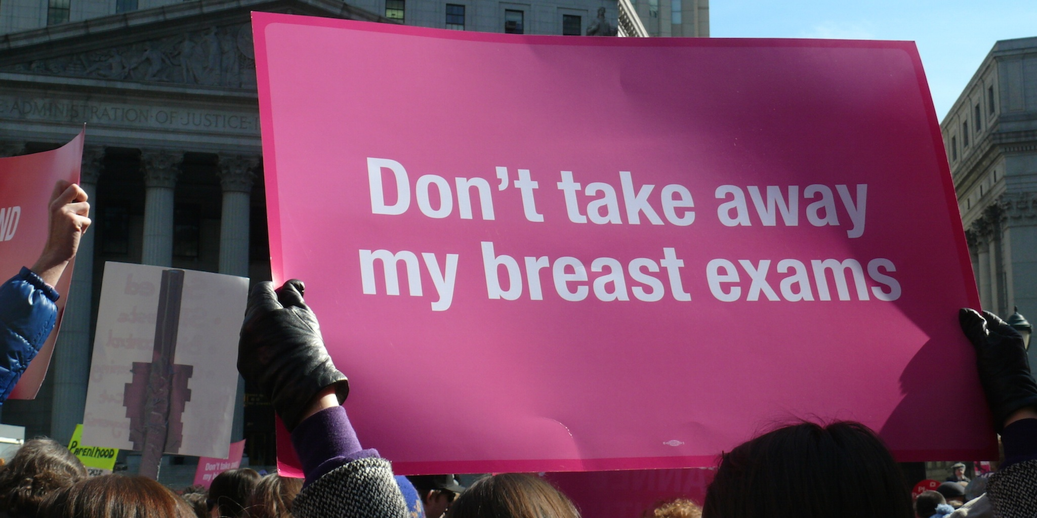 Woman holding a pro Planned Parenthood sign that reads