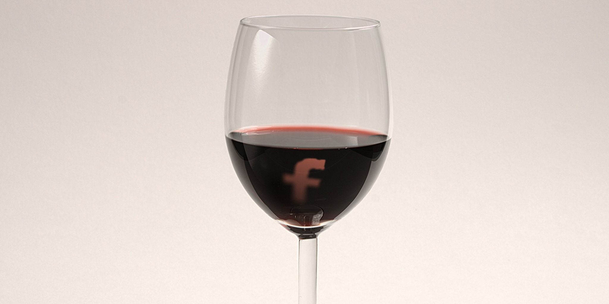 wine glass with the facebook logo floating in wine