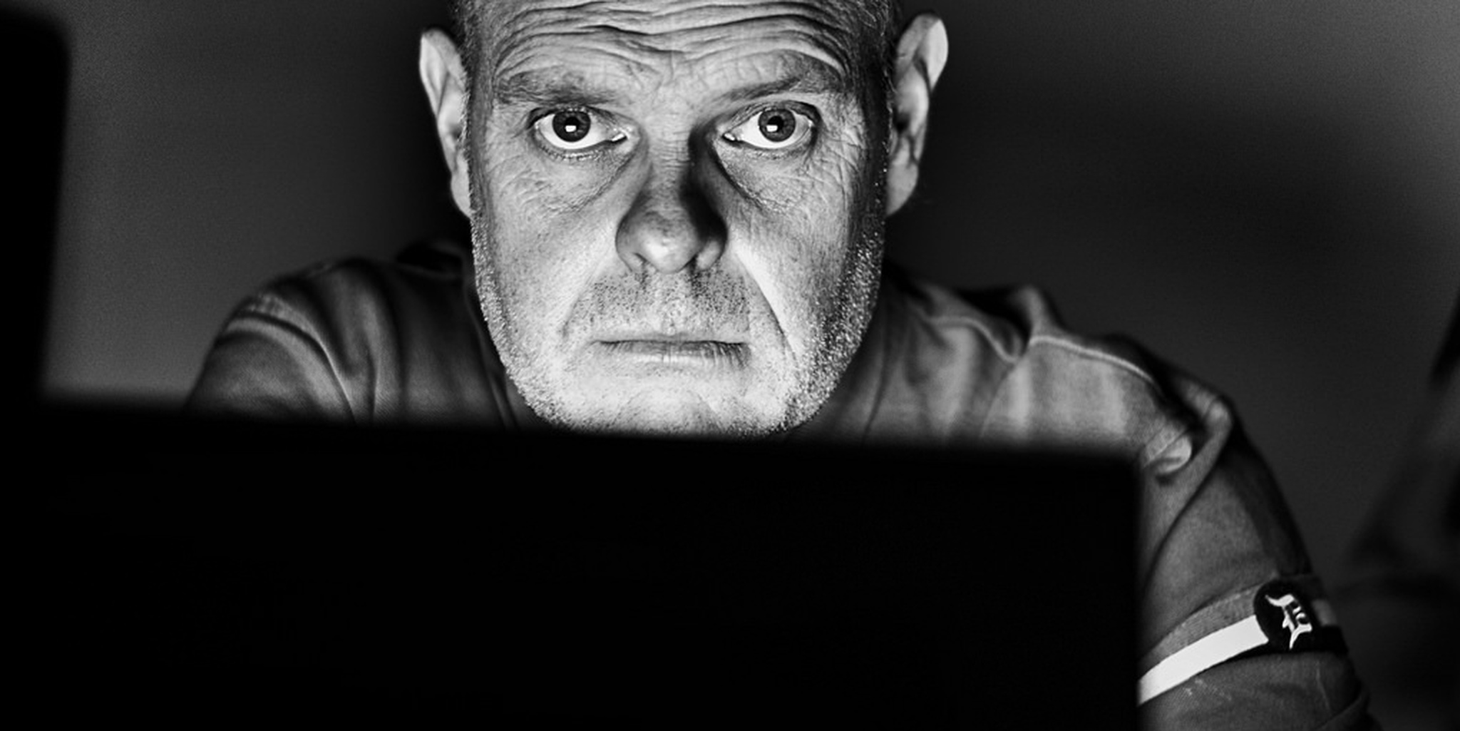 A Man Hunched Over a Laptop