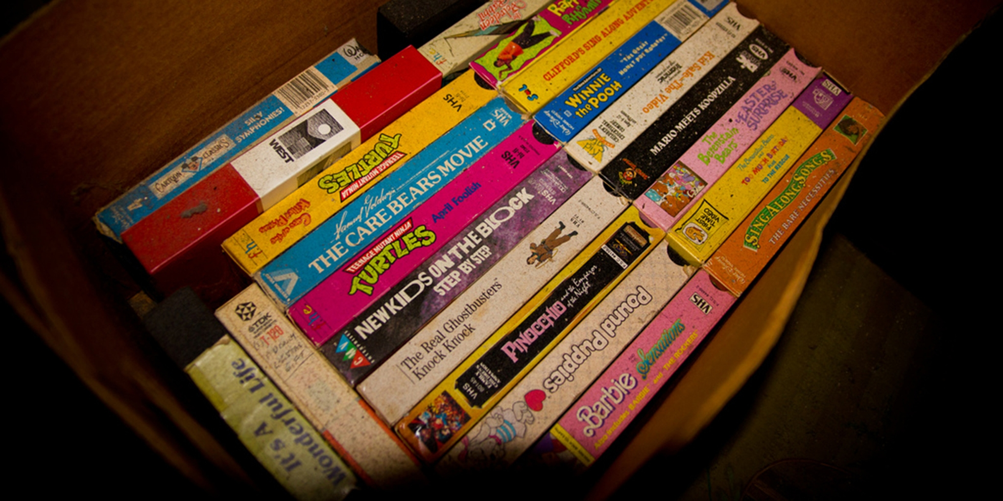 90s vhs video tapes of children's movies in a cardboard box