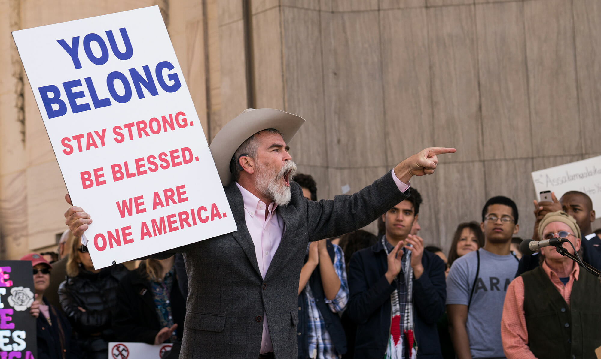 "Chain migration - Man holding ""You belong, stay strong. Be blessed. We are one America"" sign"
