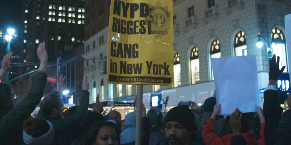 A yellow sign reads 'NYP Biggest Gang in New York' at a protest for Eric Garner