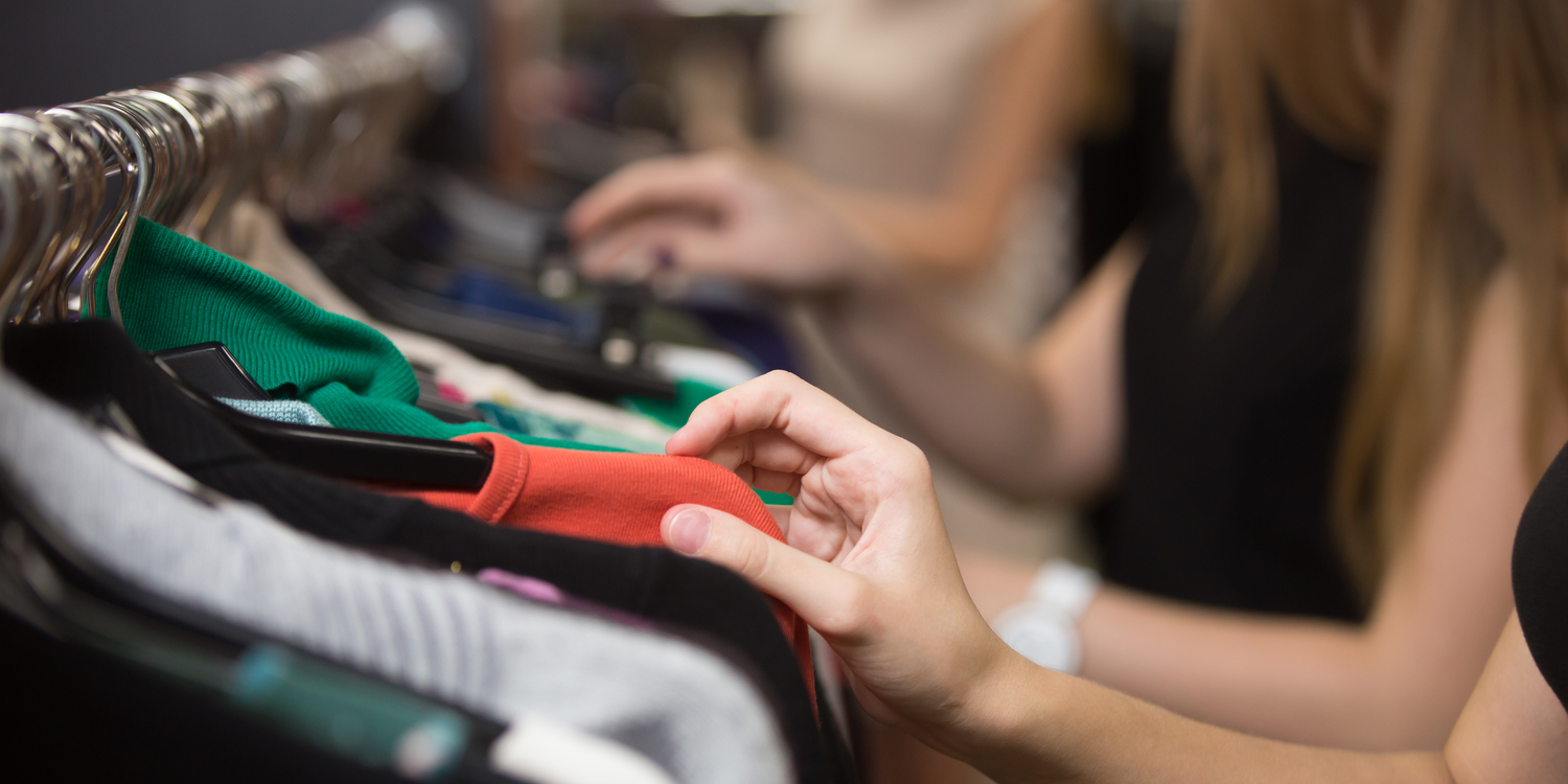 Close-up of woman's hands looking through clothing rack