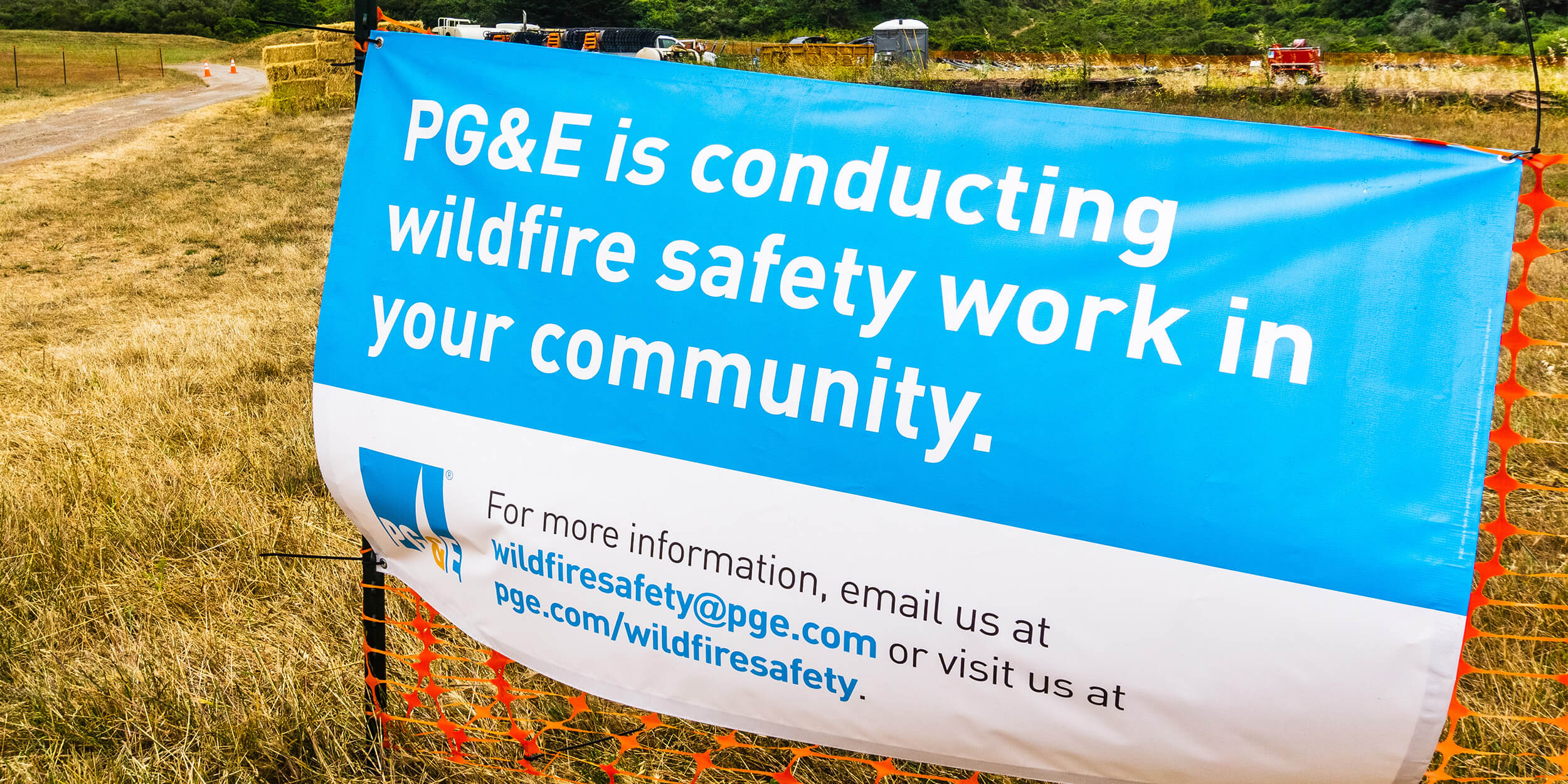 """""""pg&e is conducting wildfire safety work in your community"""" sign on construction fencing"""