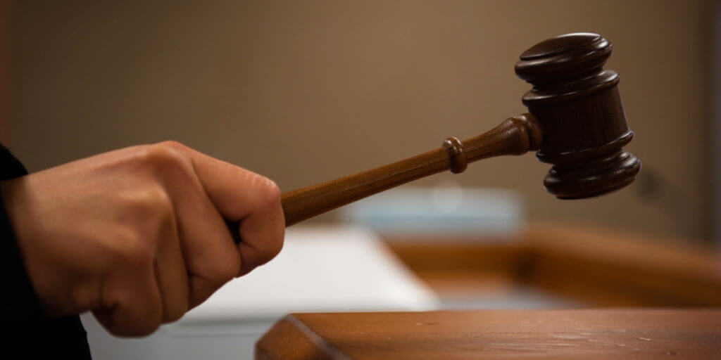 a hand holding a gavel