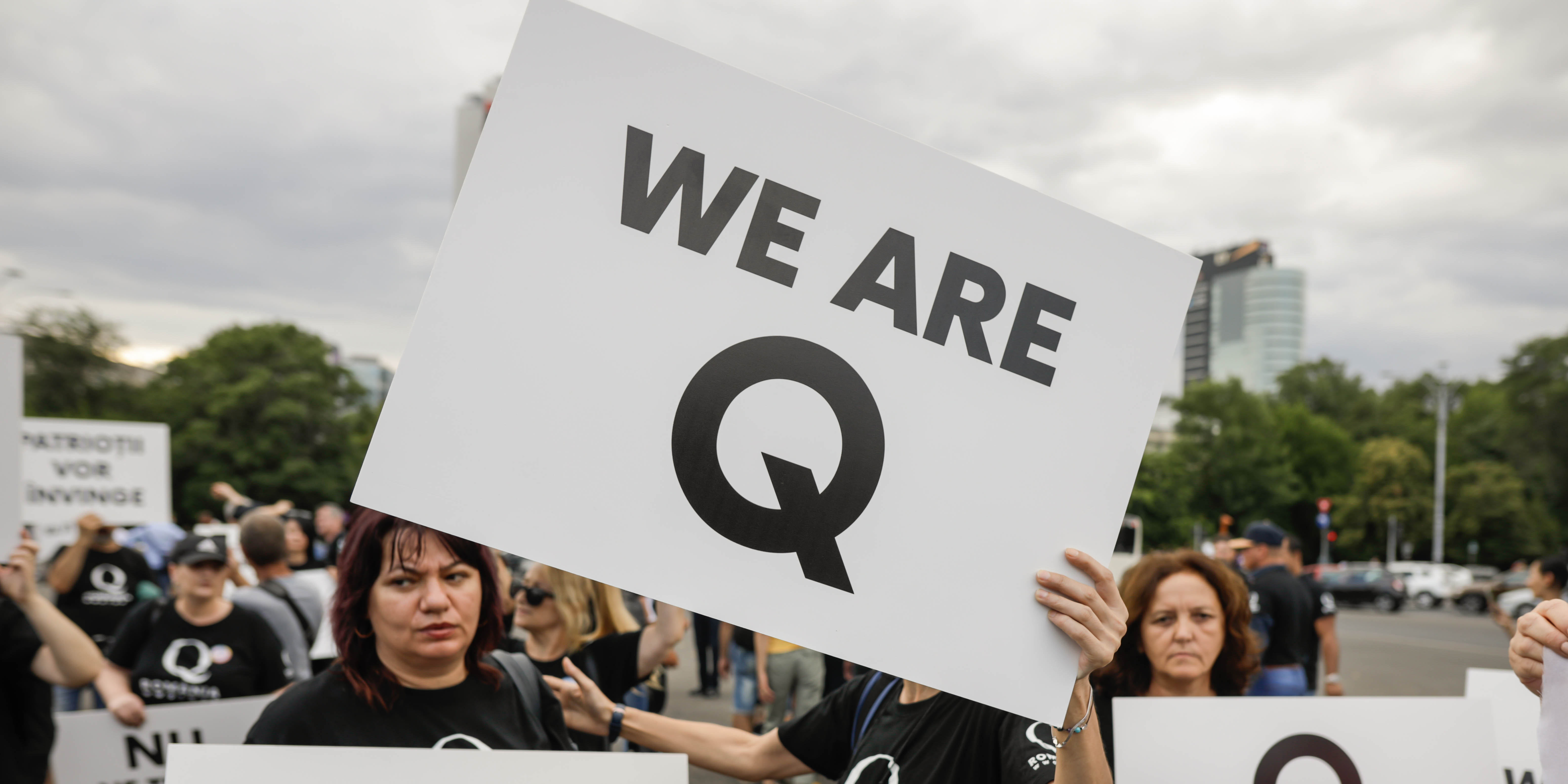 A person holding a QAnon sign that says 'We are Q'