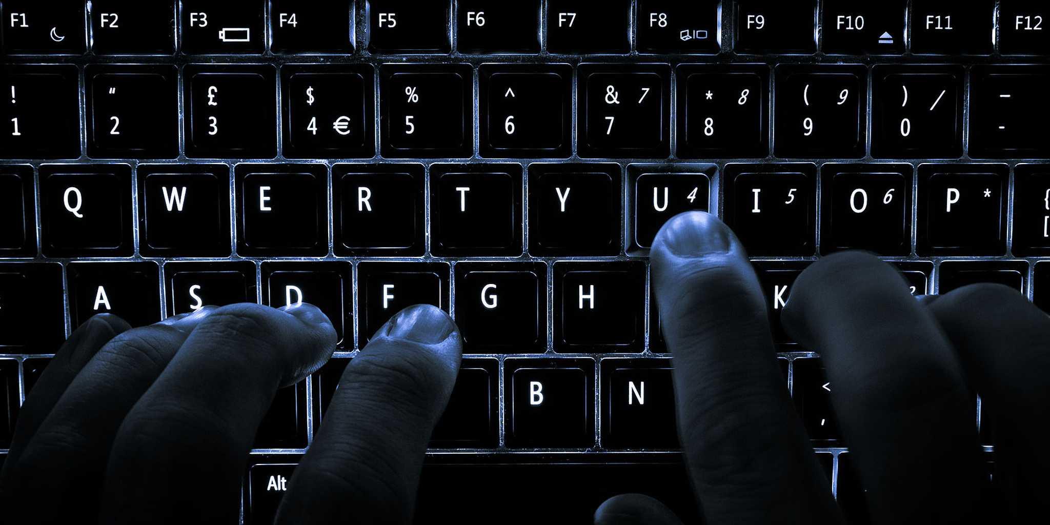 hands typing on backlit keyboard