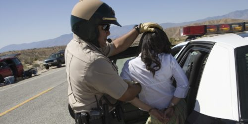 Police arresting woman on road