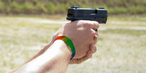 LGBT bracelet on hands aiming pistol