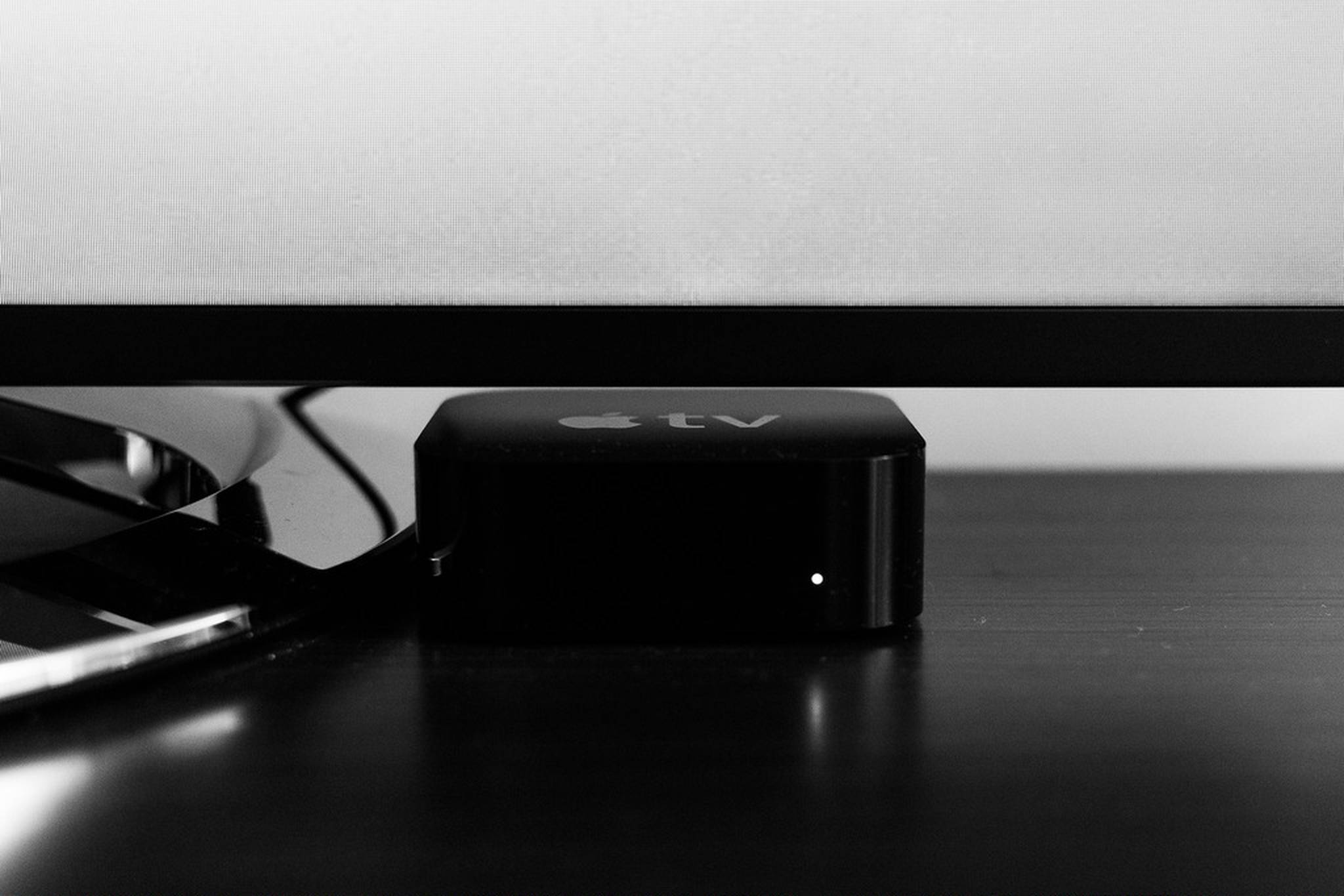 Black and white image of an Apple TV under a TV set