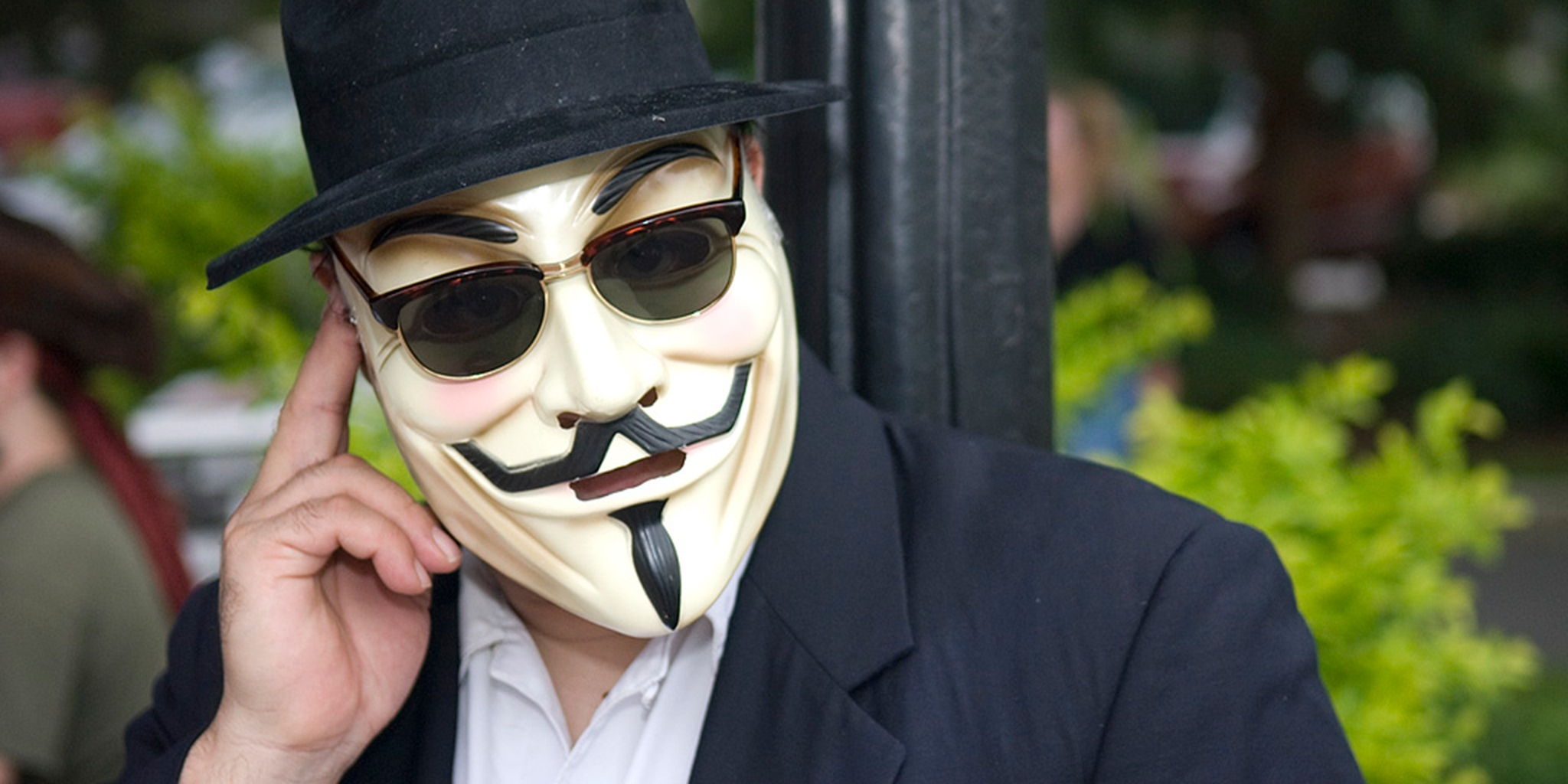 Man wearing Guy Fawkes mask with fingers up to ear