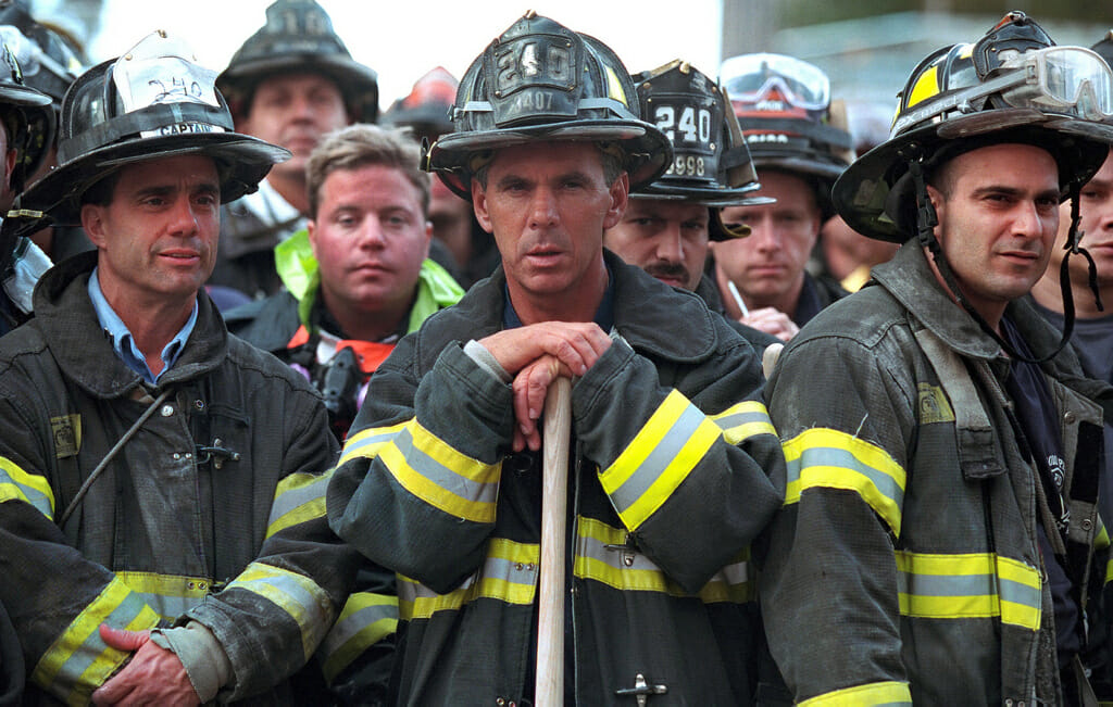 Firefighters look on Friday, Sept. 14, 2001, as President George W. Bush surveys the destruction left by terrorist attacks on New York City. Photo by Paul Morse, Courtesy of the George W. Bush Presidential Library