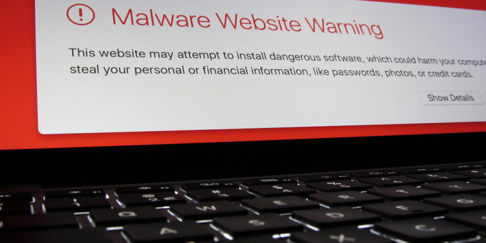 Image of malware website warning above a keyboard