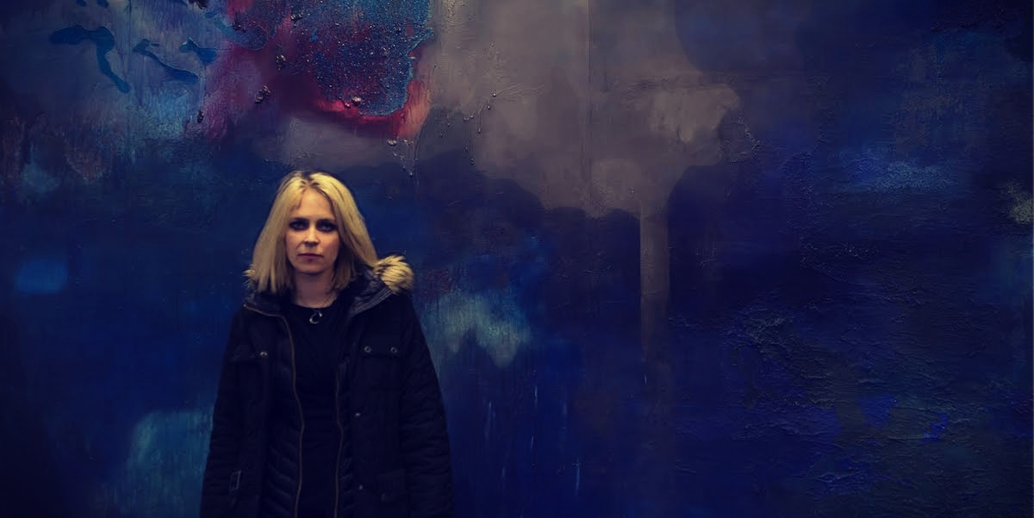 Sara, the head of the Icelandic protest movement, standing in front of painting.