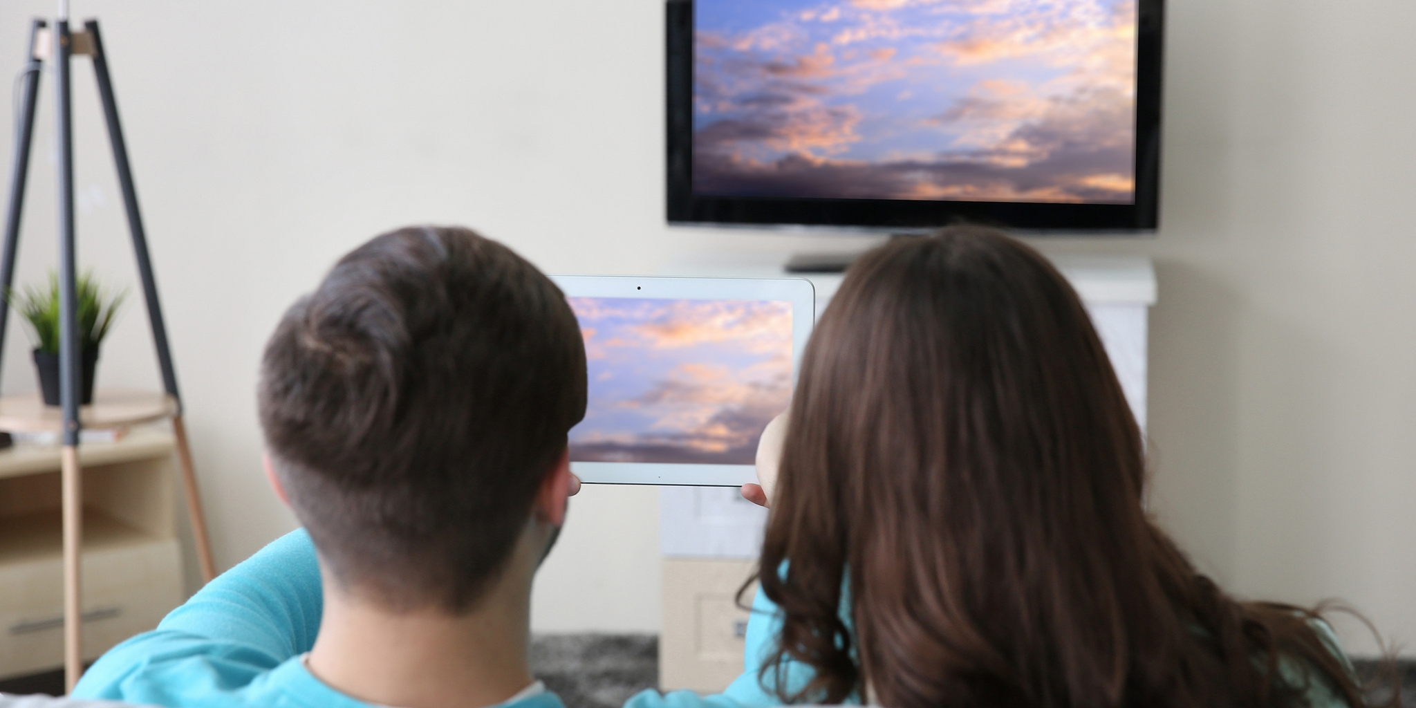 couple looking at picture on both ipad and tv