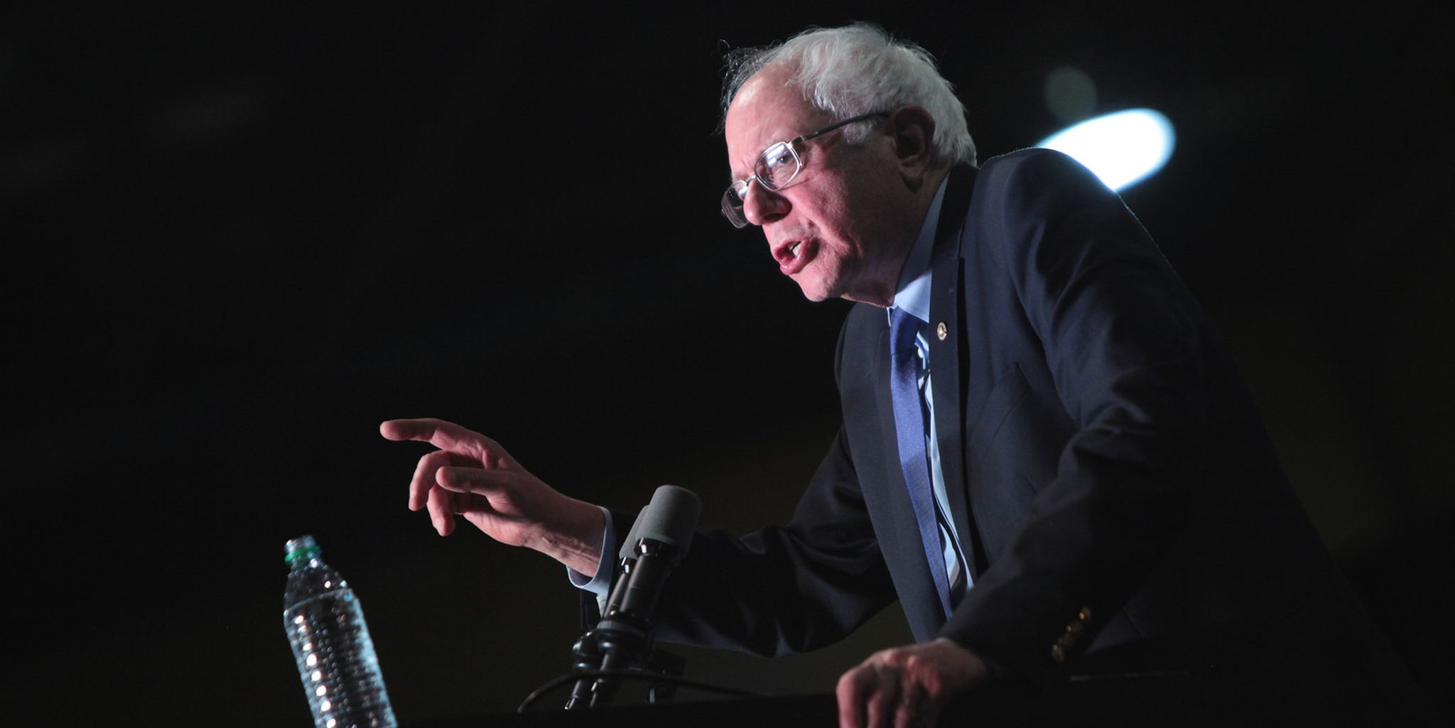 Bernie Sanders standing on stage with his finger pointing